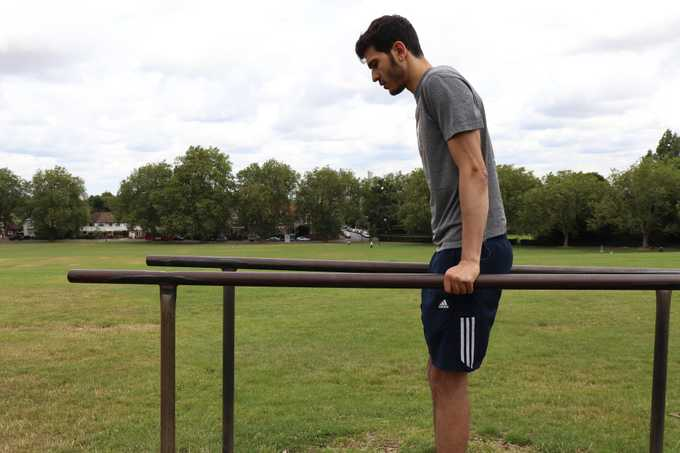 Person performing a parallel bar dip
